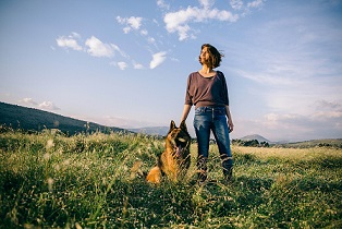 A woman and her shepherd dog in an open field