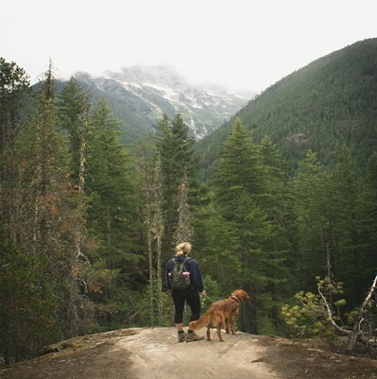 A hiker and her dog enjoys the view from the mountaintop